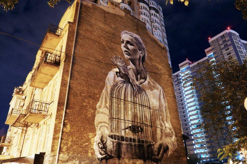 Мурал «Девушка с птицами и клеткой» на улице Антоновича ночью.
